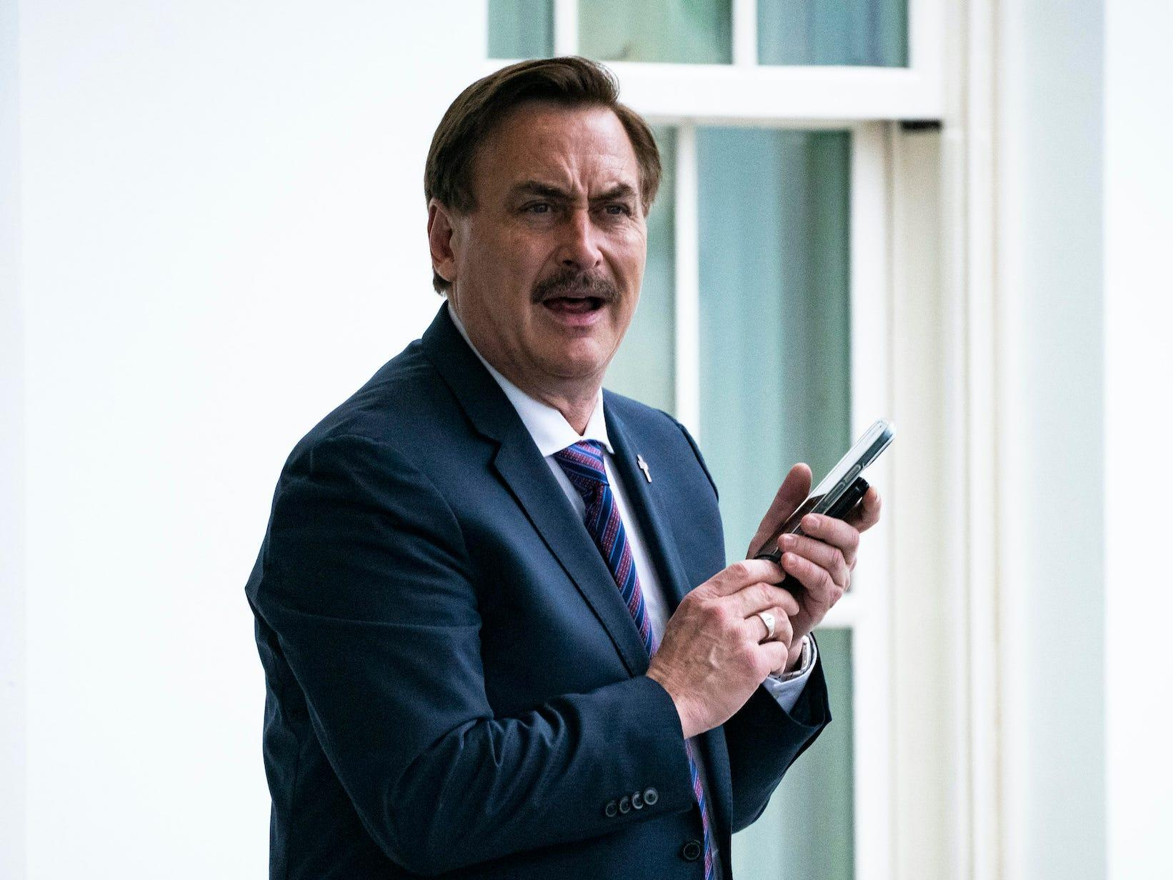 <div><figure><div><div><p><img alt=Mike Lindell holds a phone to his ear outside the Wh